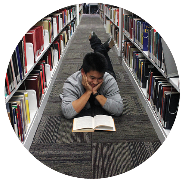 Heat Soccer player Jordan Lam reads on the floor of the UBCO Library. Photo by Lynnette Oon